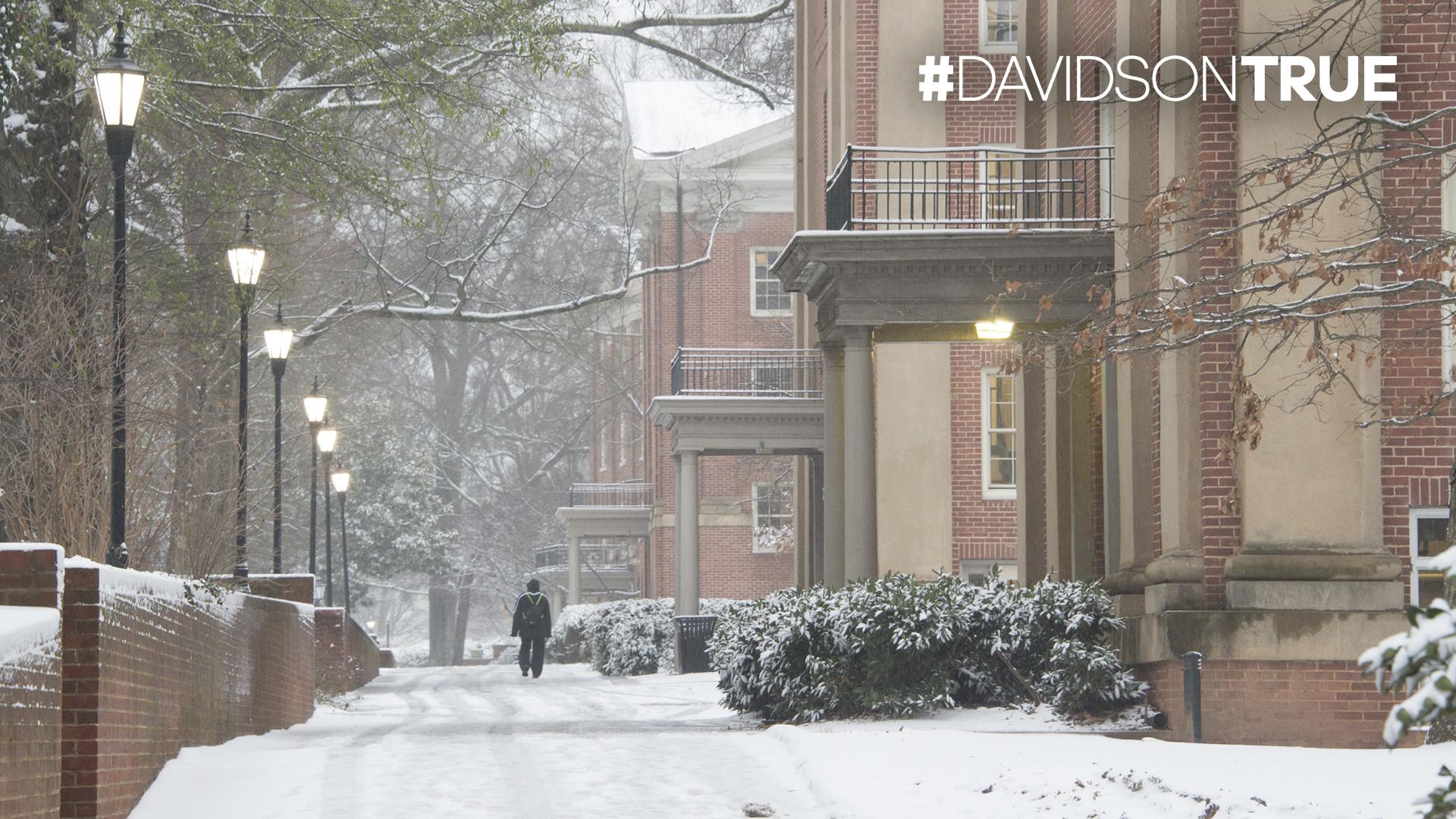 Students along snowy dorm row with Davidson True wordmark
